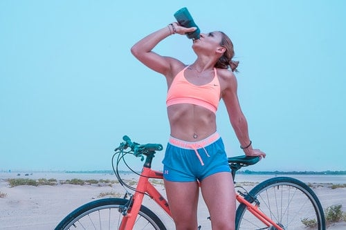woman enjoying her fitness routine drinking water