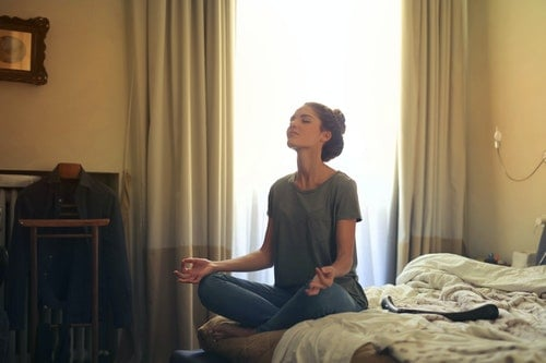woman sitting on bed using mindfulness