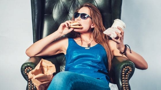 woman mindlessly eating junk food on a chair