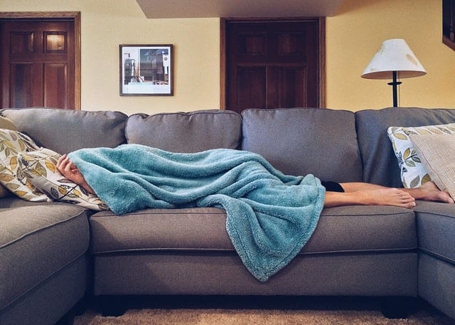 man napping on the couch under a blanket