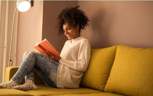 woman with good reading habits sitting on couch with a book