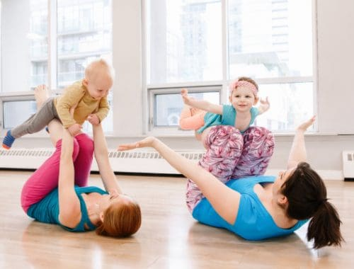 two women work out with toddlers