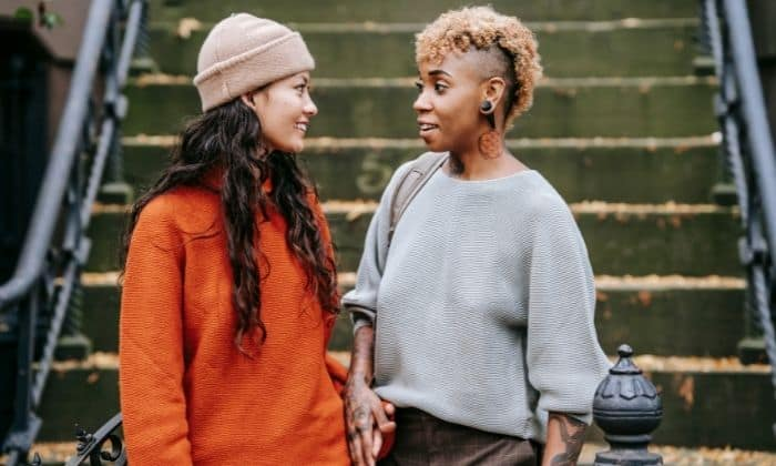 ENFP woman and INTJ woman having a discussion on the steps