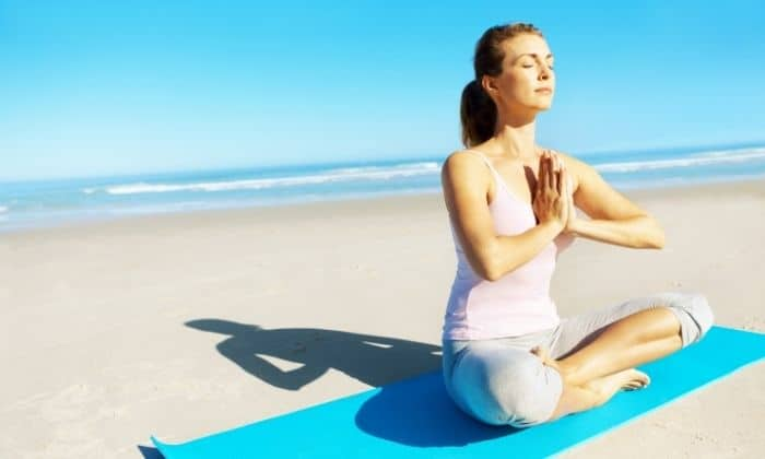 woman meditating and relaxing on beach