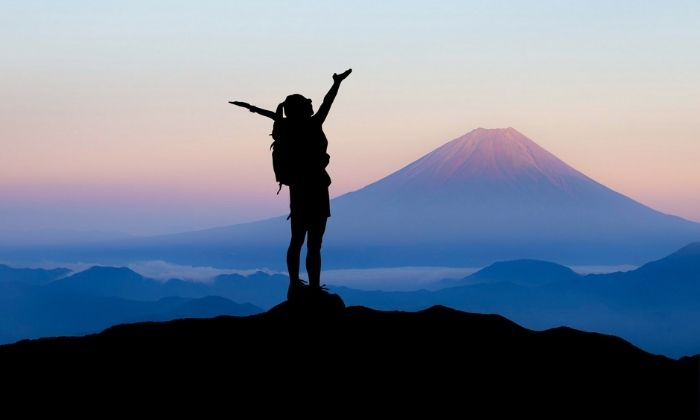 woman raising hands on mountain from dreams vs goals